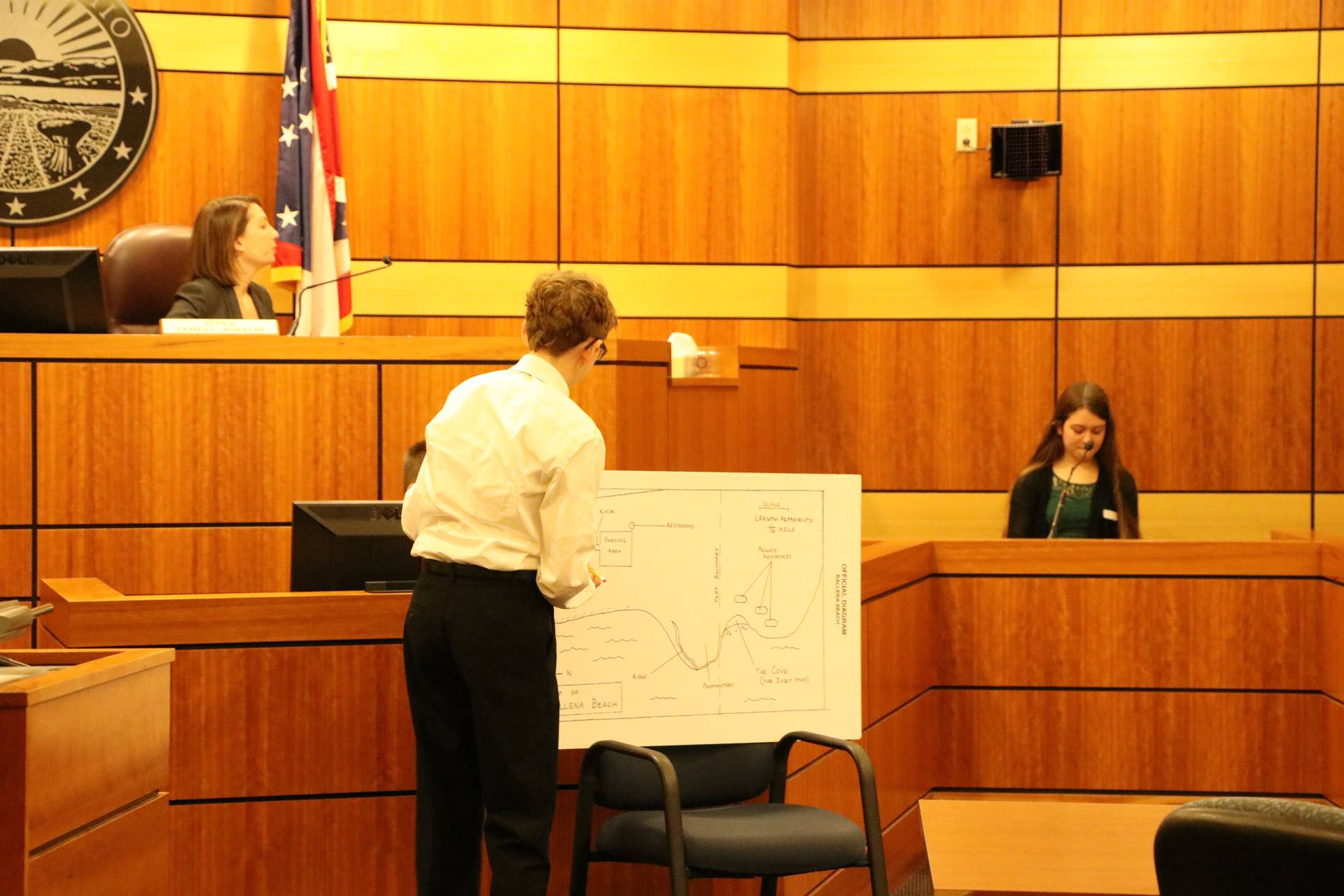 boy writing on poster diagram in court room
