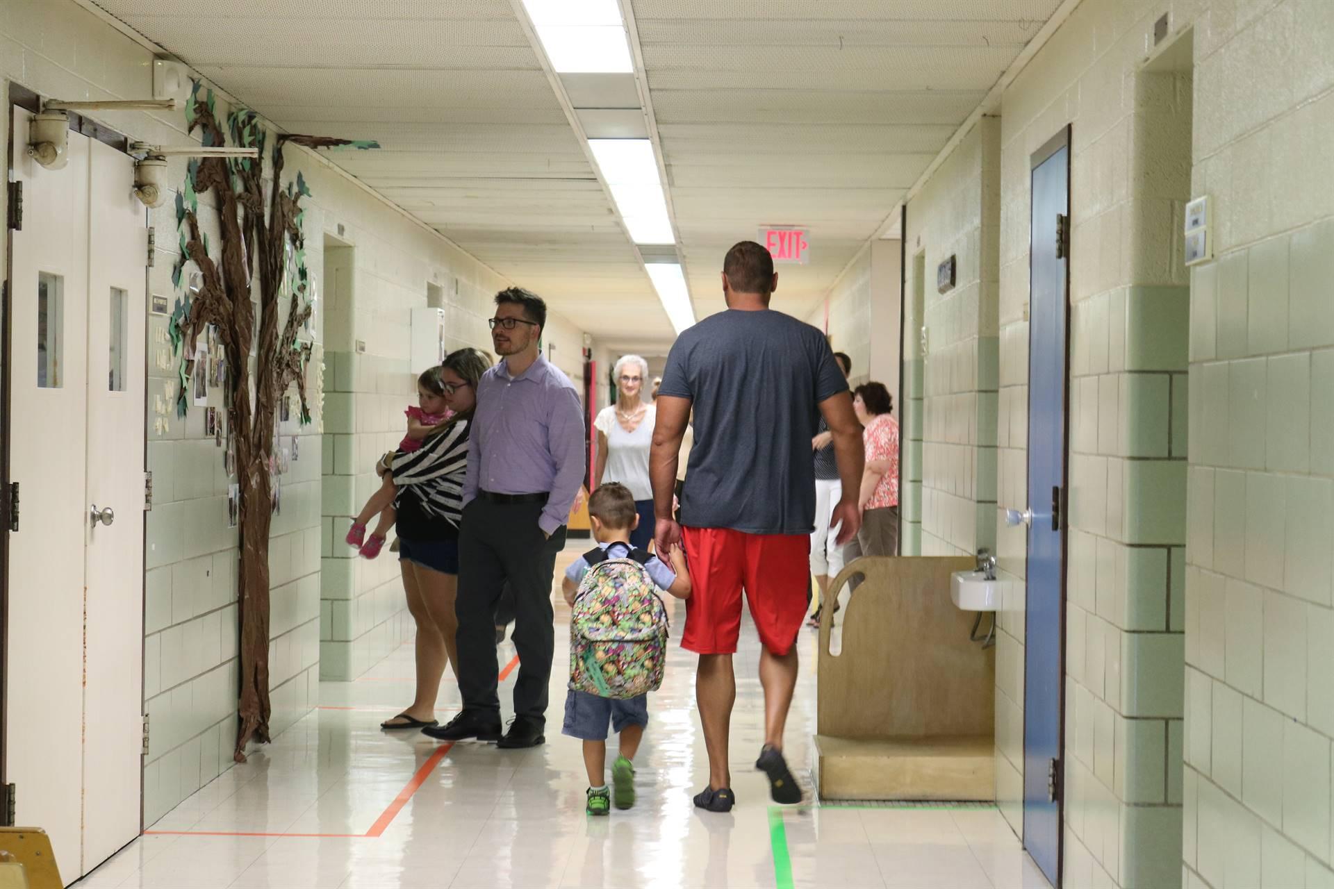 2 males, 1 female walking boy in hall