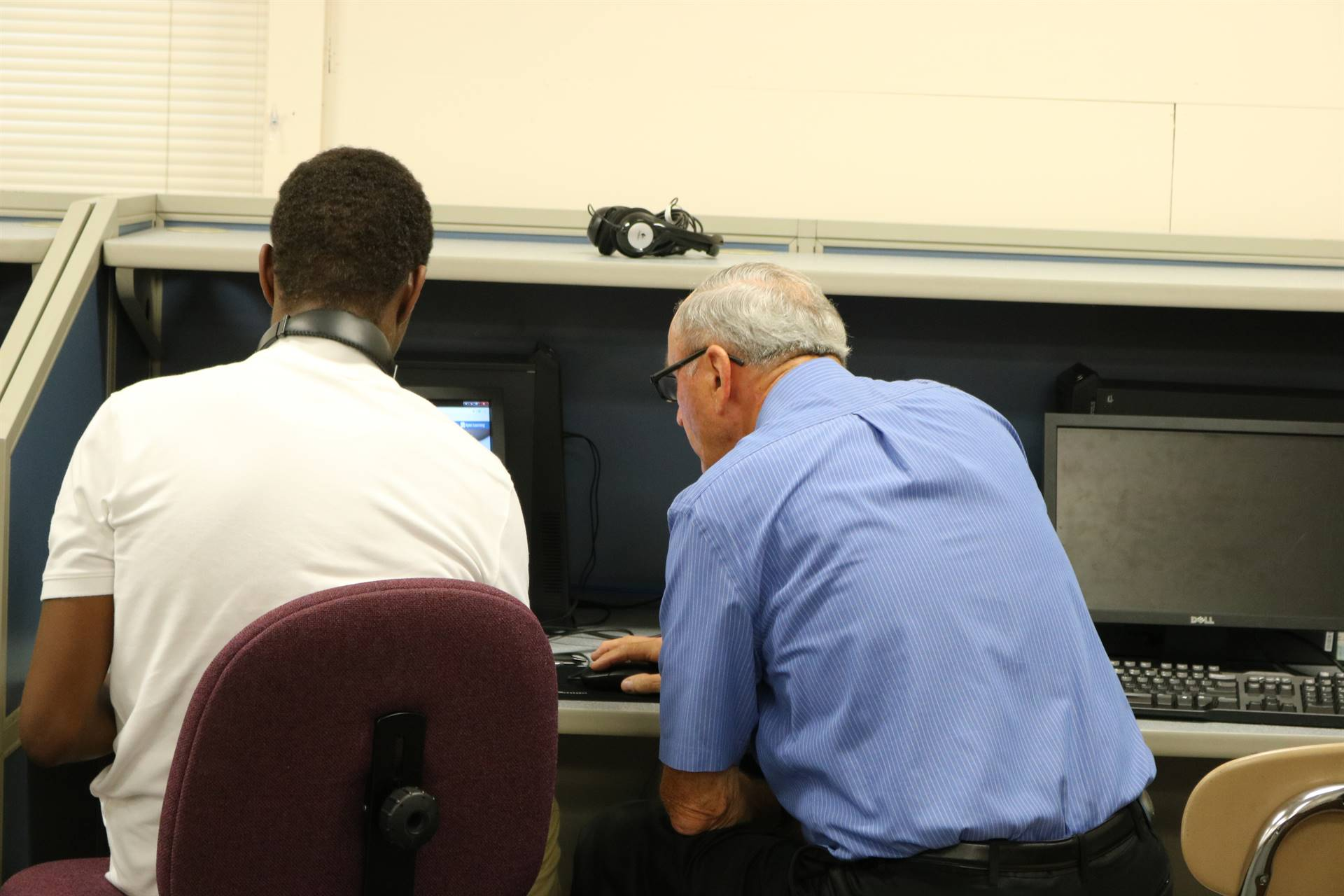 male teacher working with male student on computer
