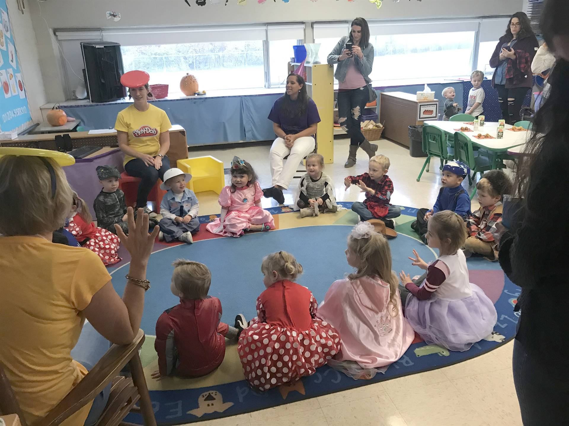 pre k class with costumes on floor in circle