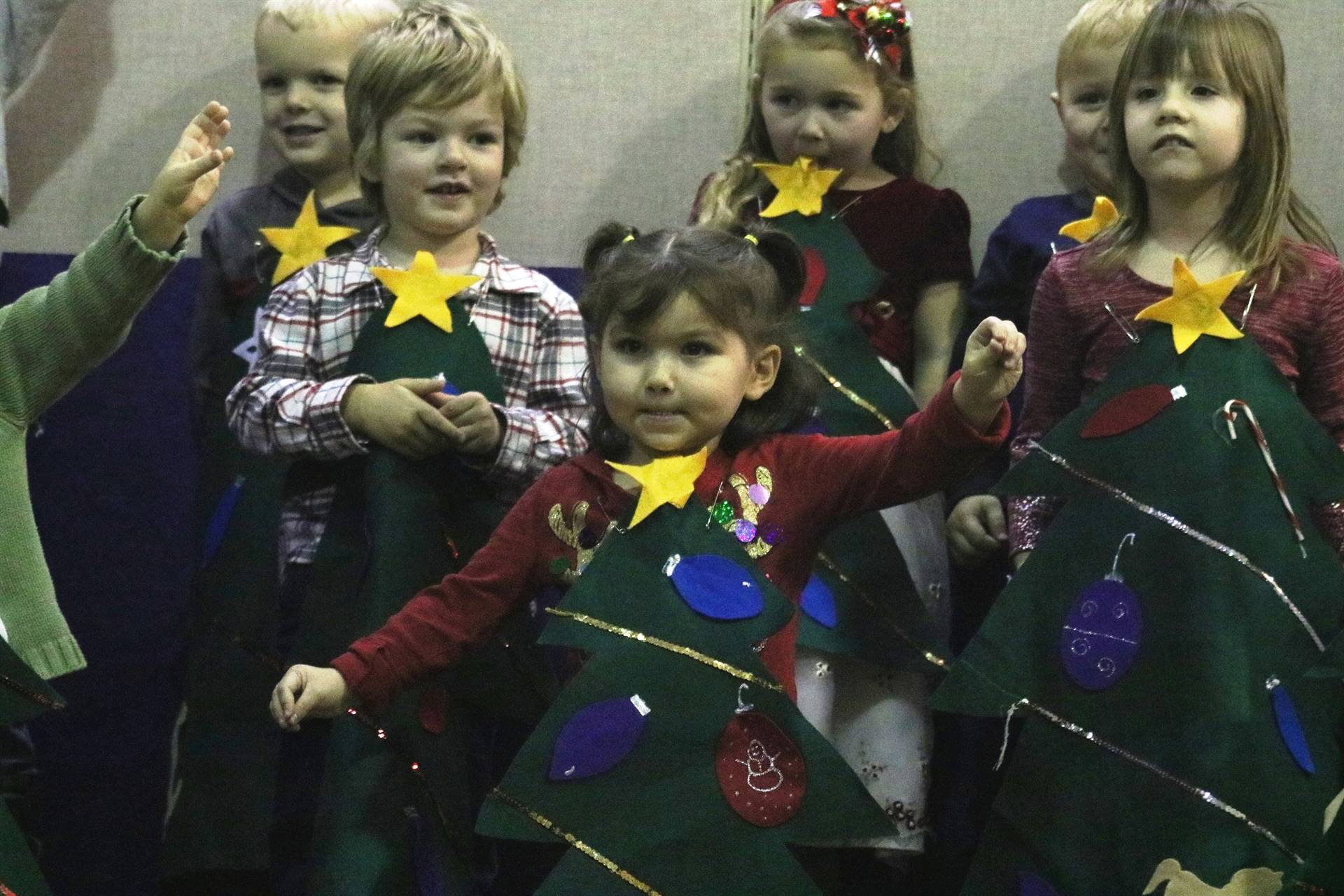 group of preschoolers singing with felt Christmas tree on the front of shirts