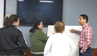 3 females talking to a male who is pointing to a white board