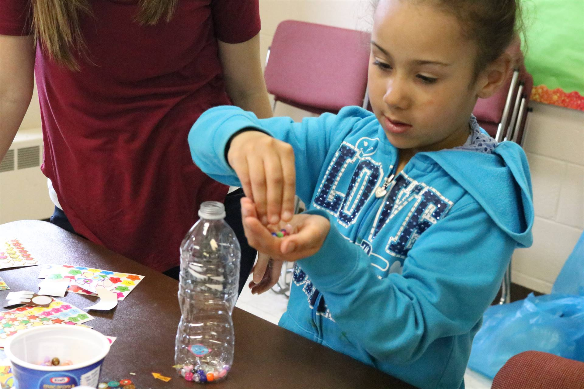 girl putting beads in empty bottle