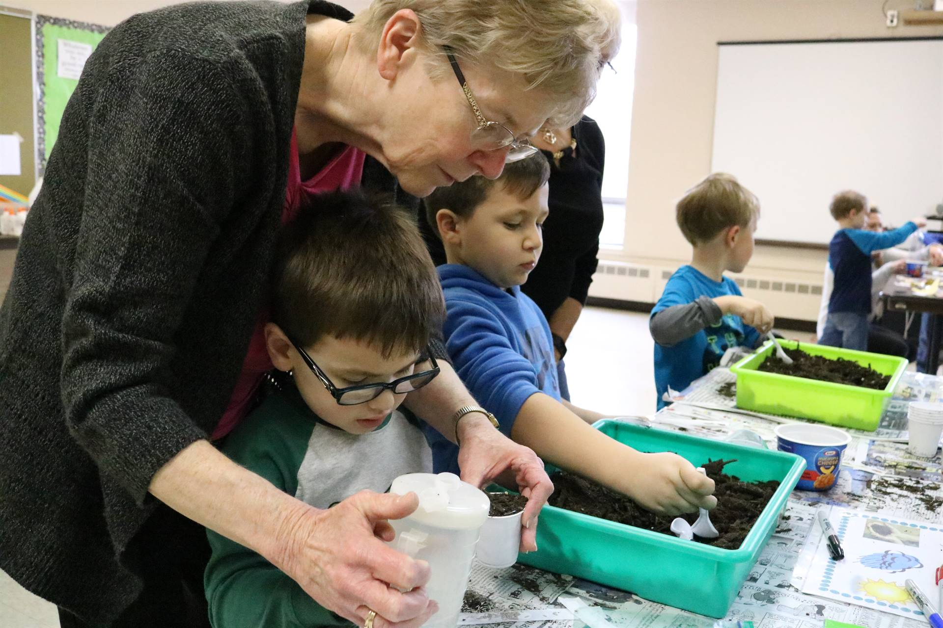 lady with 2 boys with dirt in cups