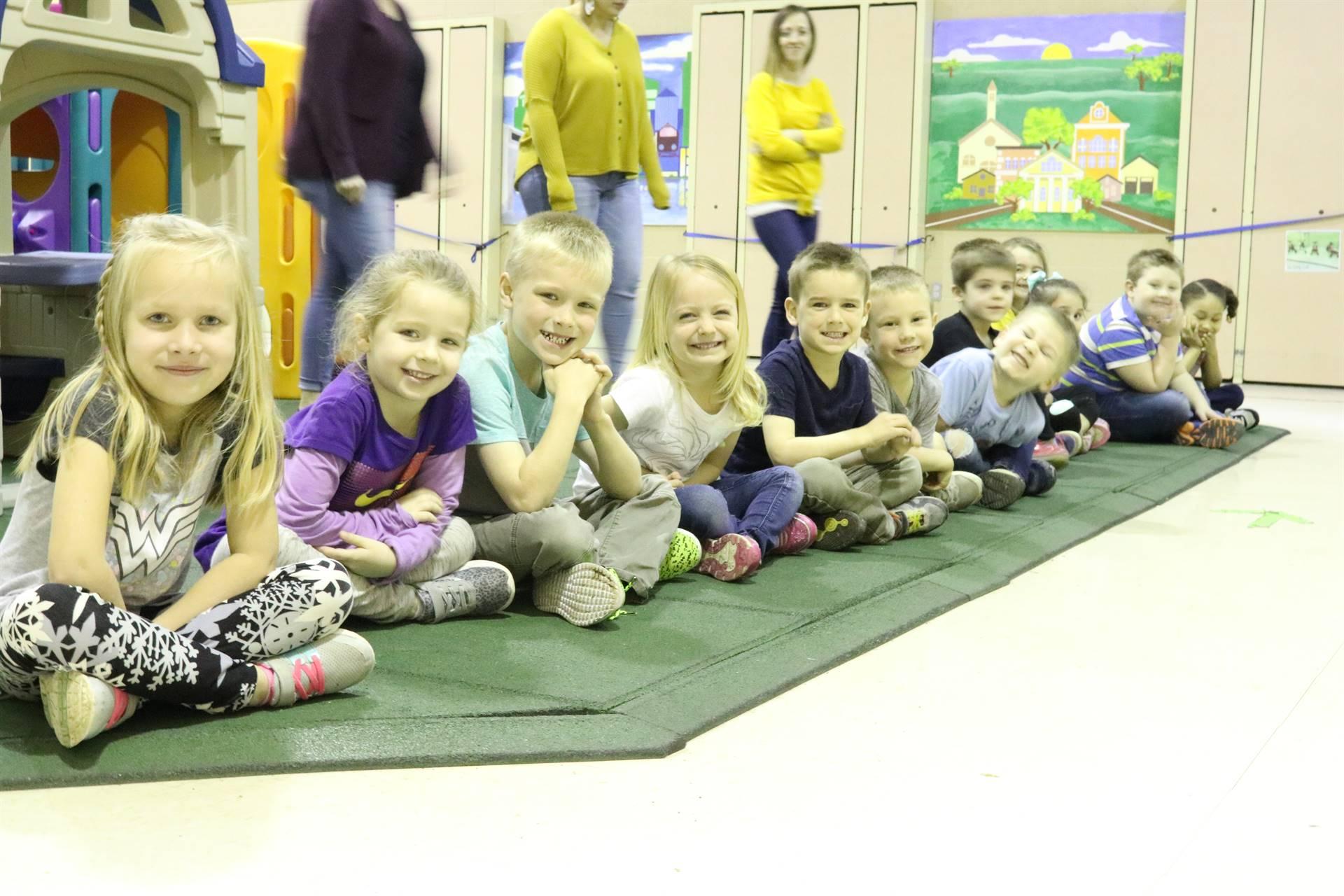 line of 12 kids sitting on floor