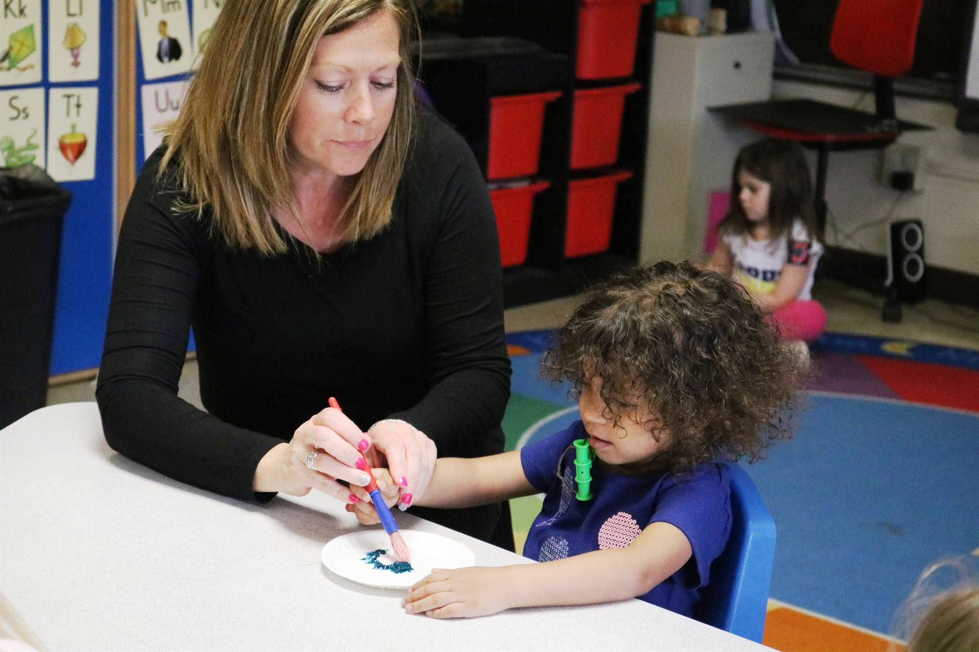 teacher lady with girl painting at table