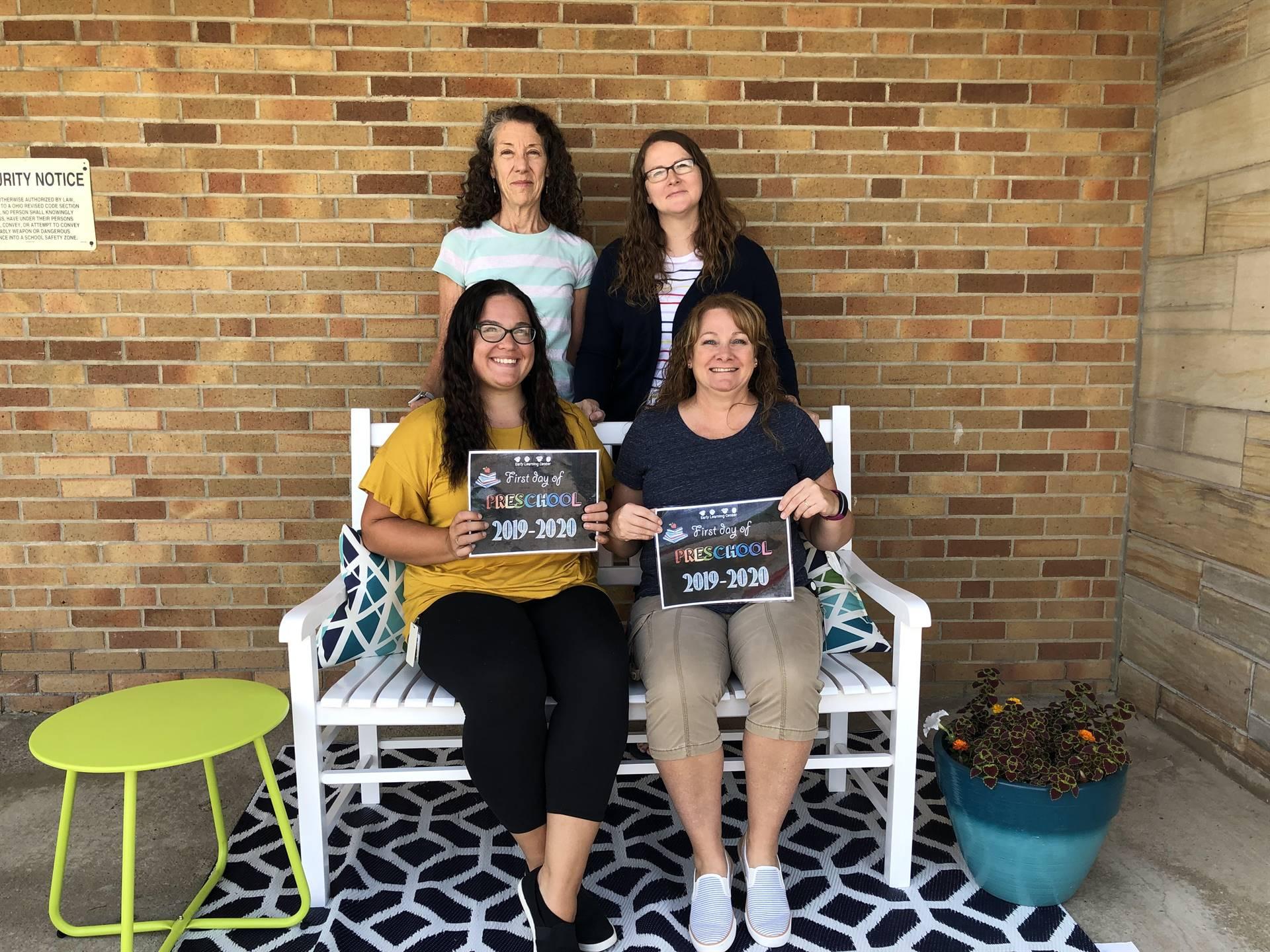 4 ladys sitting on bench