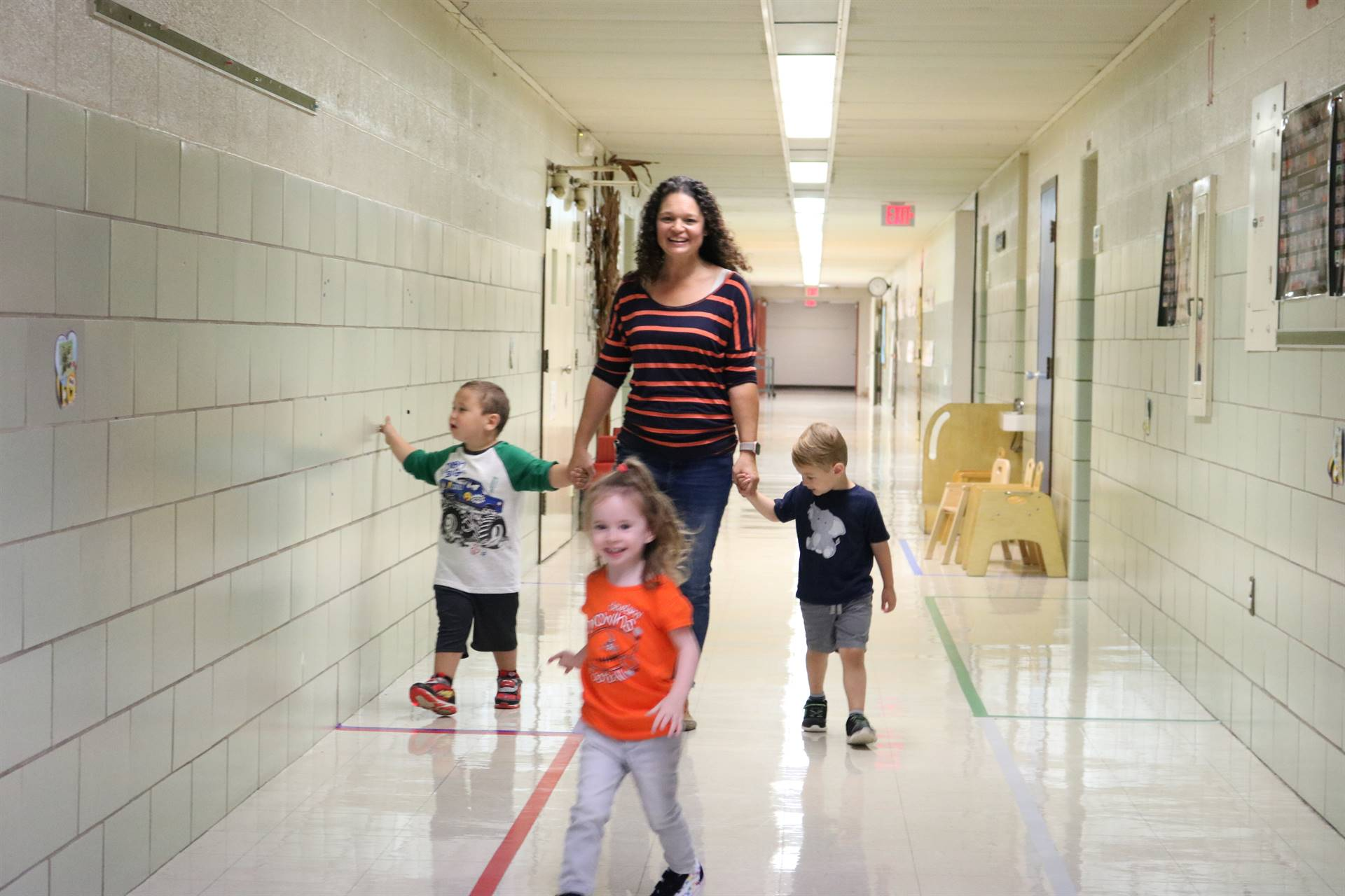 lady walking down hallway with 2 boys 1 girl