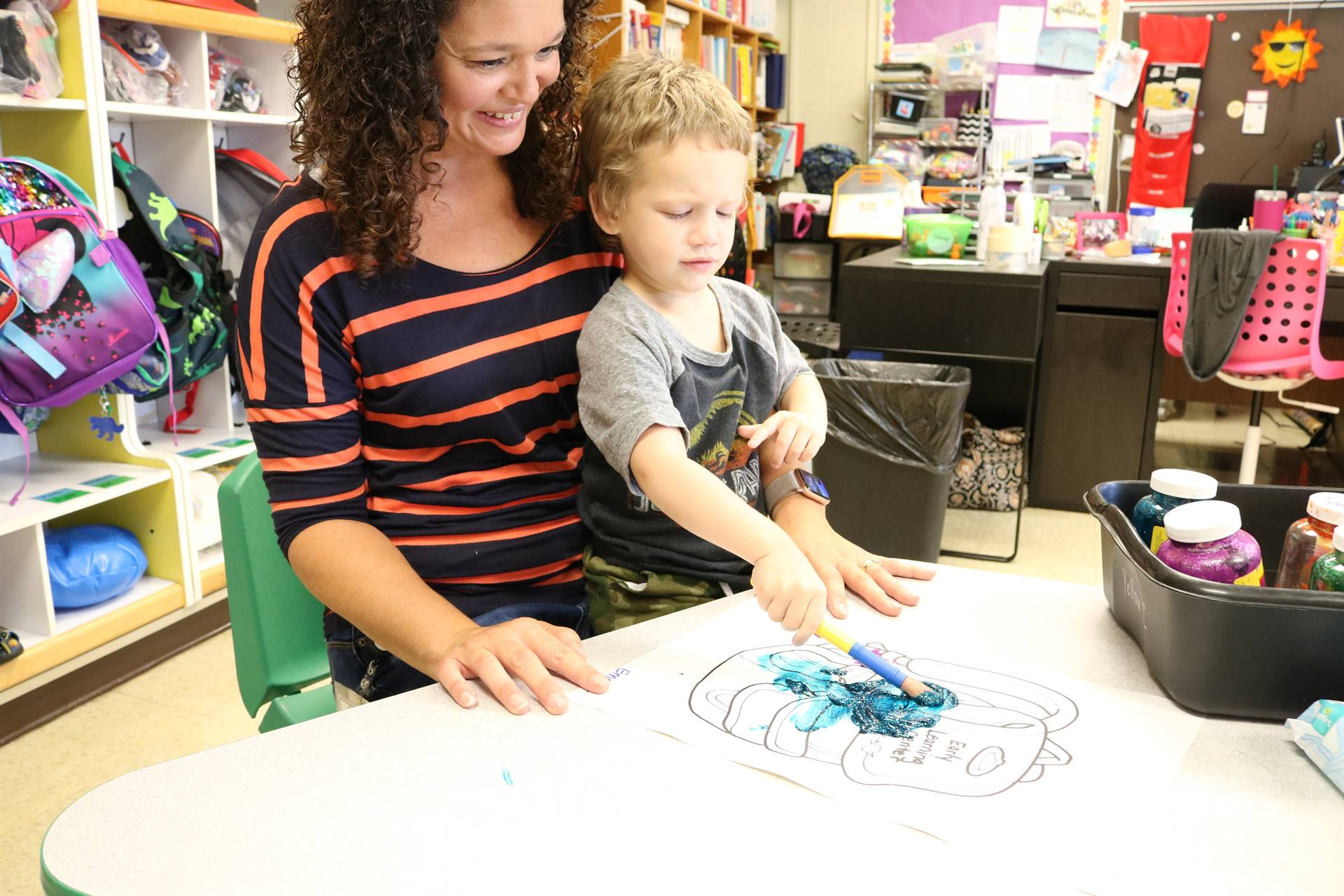 teacher holding boy painting