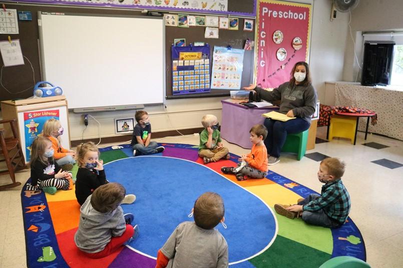 KIDS SITTING IN A CIRCLE TEACHER TEACHING