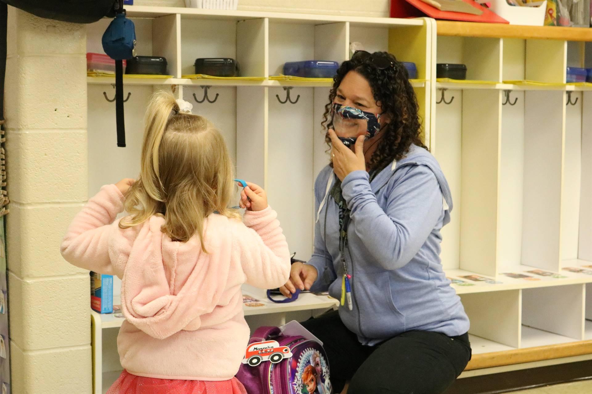 girl talking to lady teacher