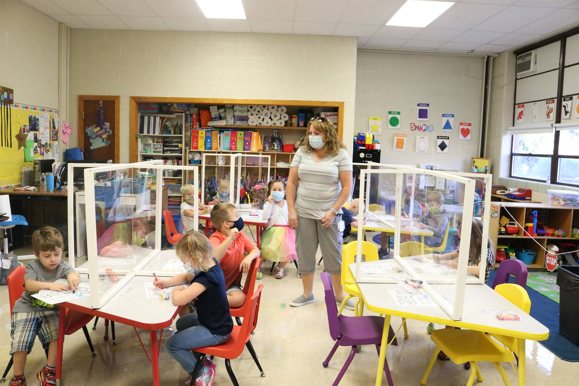 teacher standing in middle of room with kids at tables