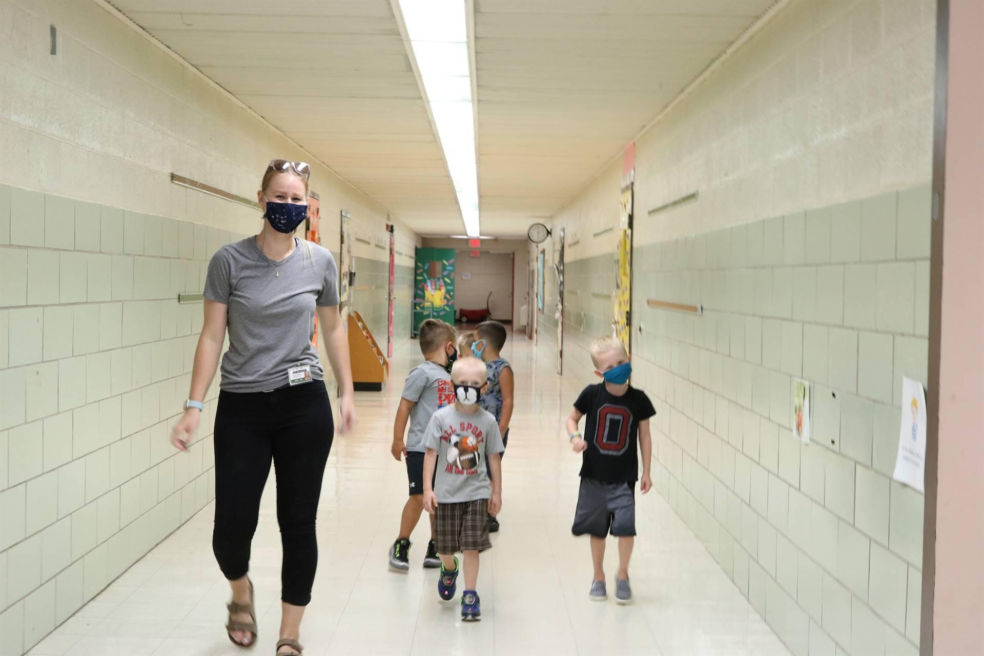 teacher walking in hall with 3 boys