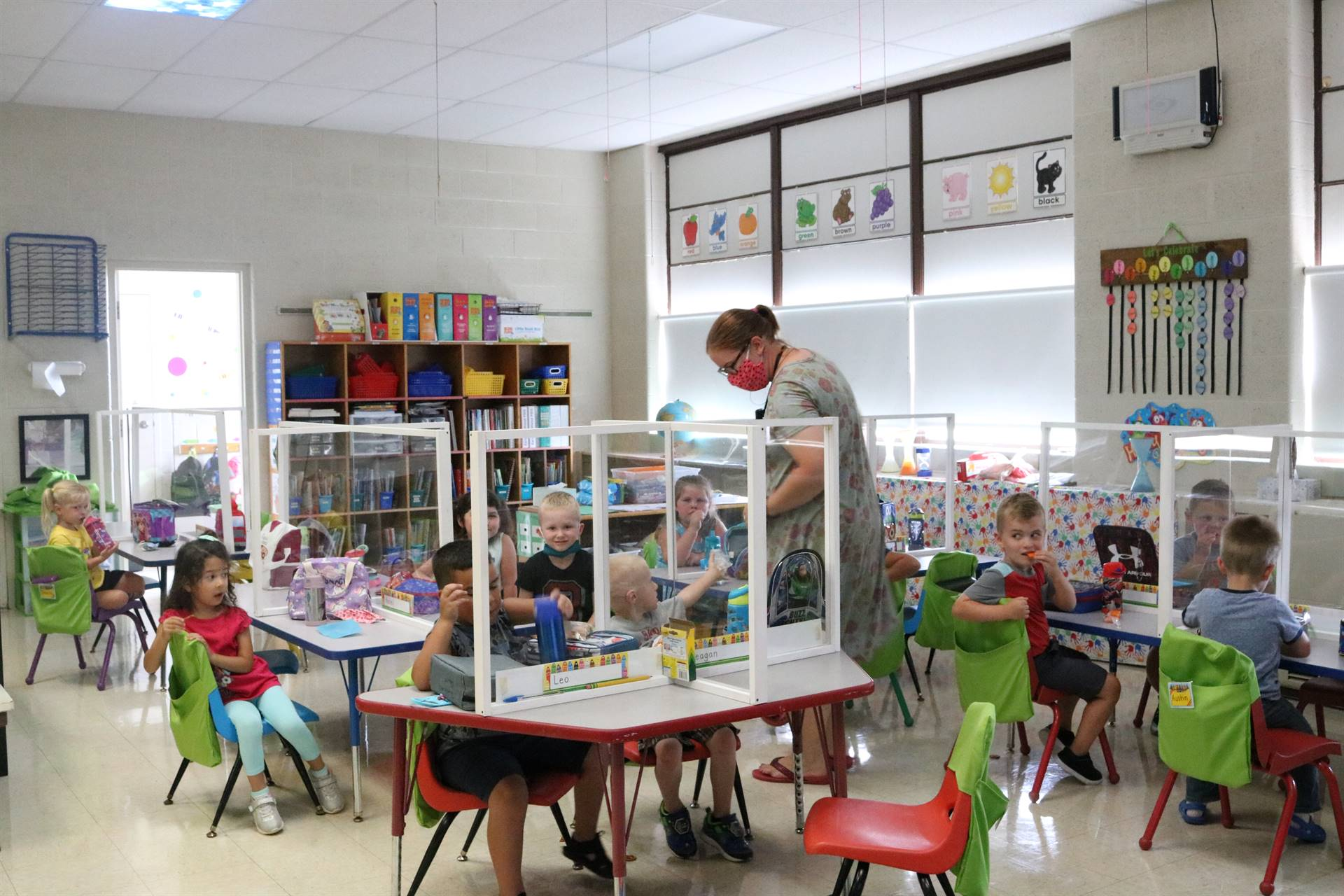teacher with kids sitting at tables
