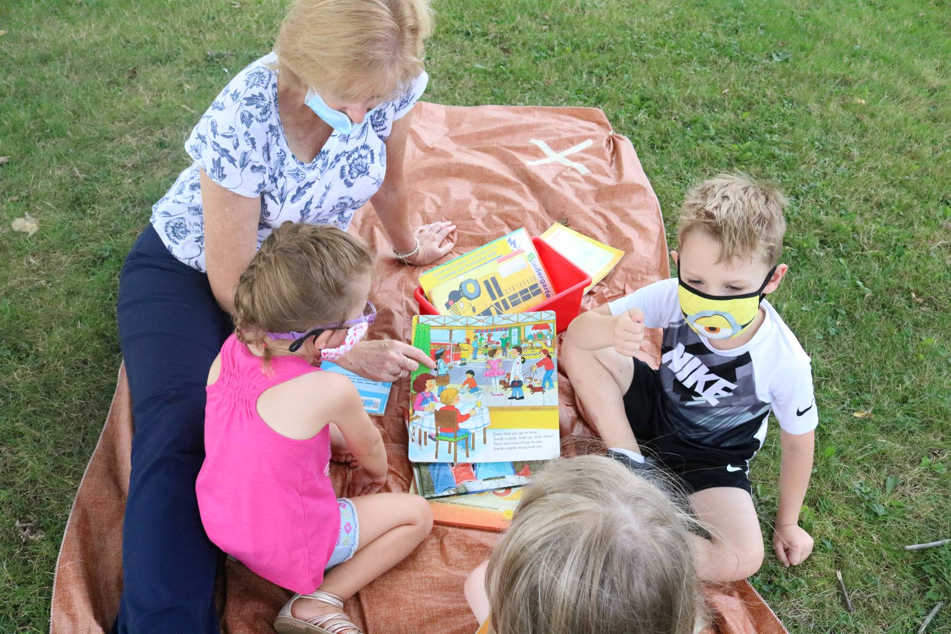 teacher reading to 3 kids