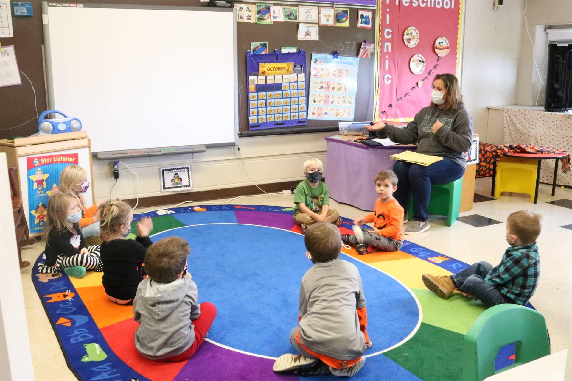kids on floor teacher sitting