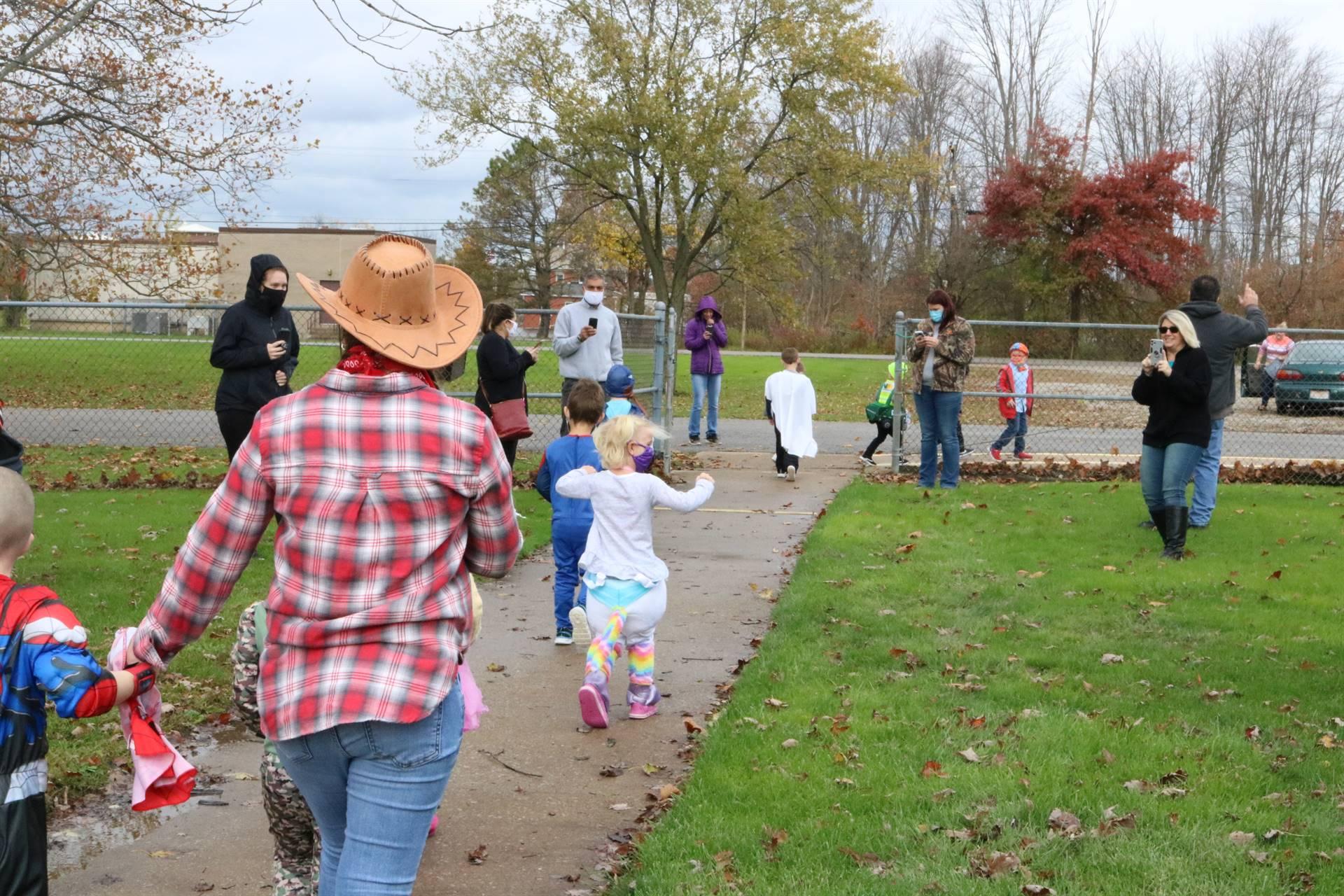 kids walking on sidewalk dressed for halloween