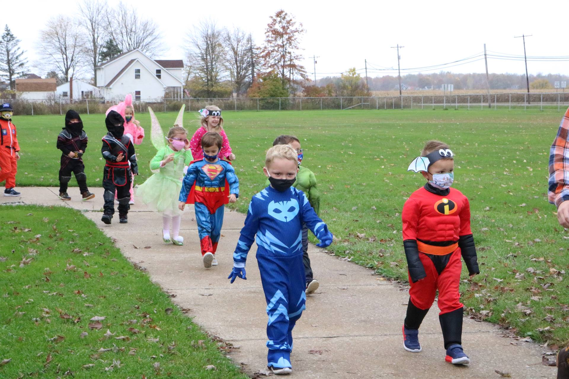 kids walking on sidewalk dressed up