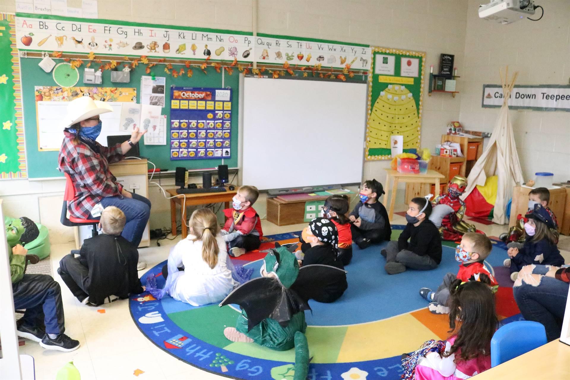 teacher reading a book to kids sitting on floor