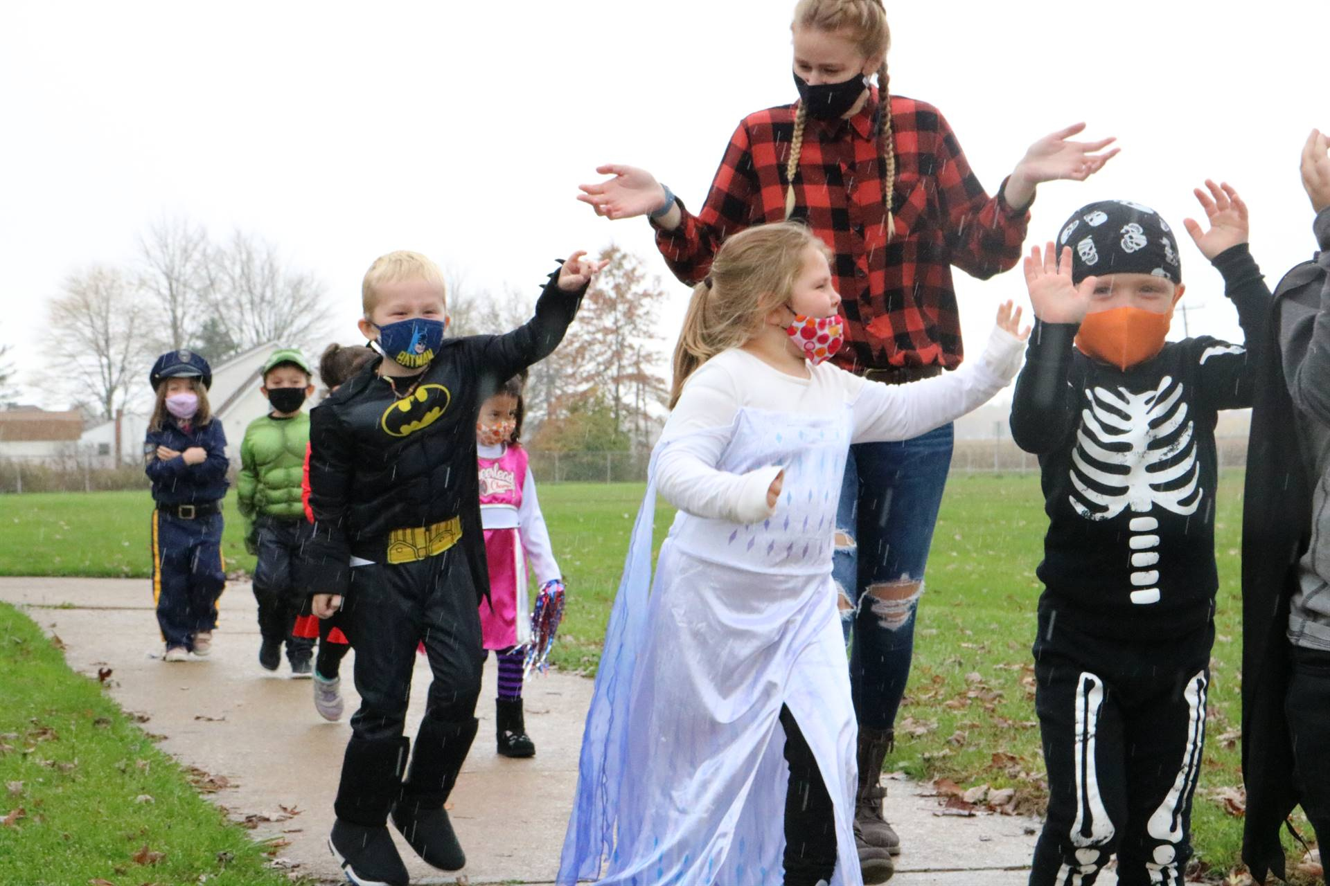 kids dressed up walking on sidewalk