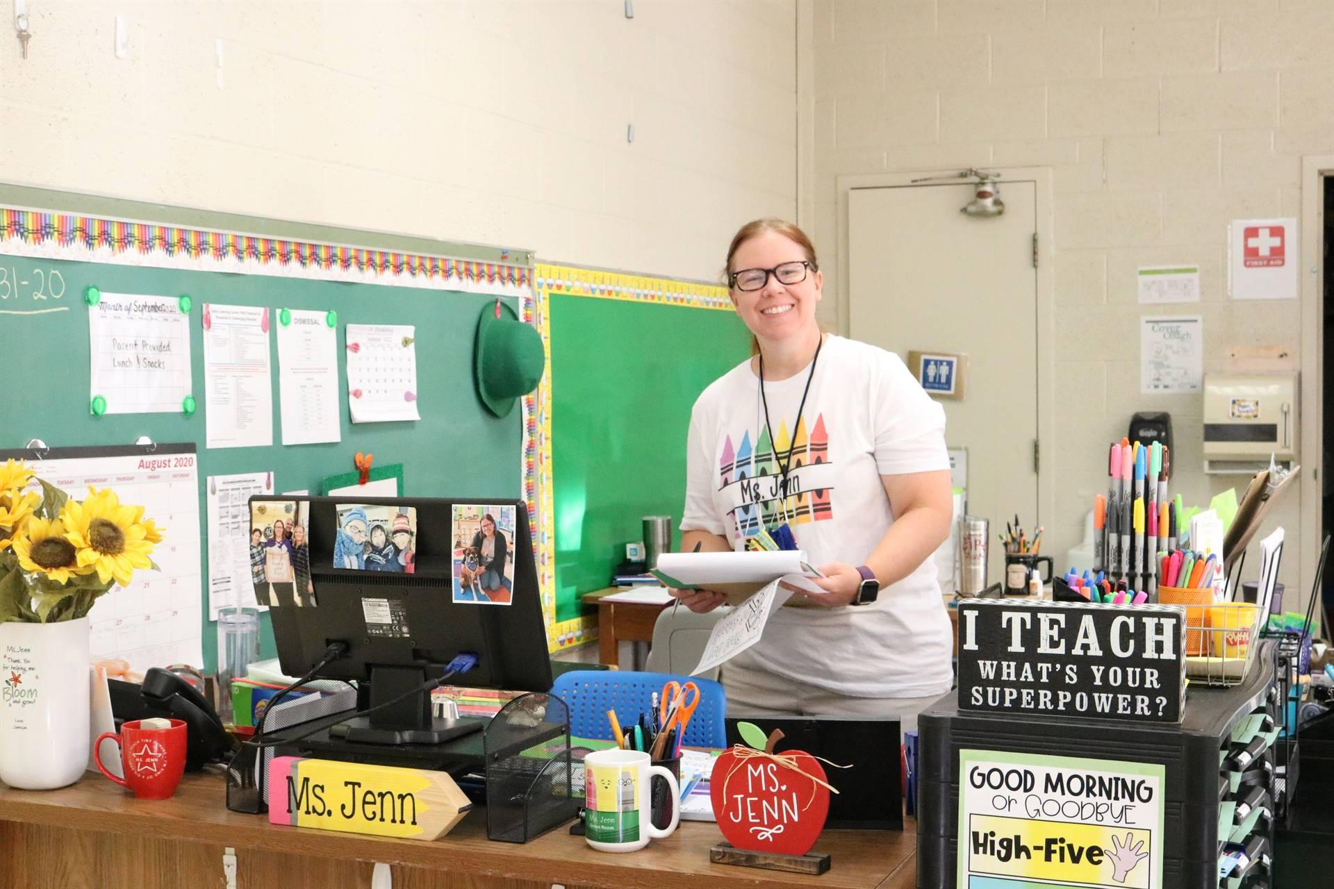 teacher standing at desk smiling