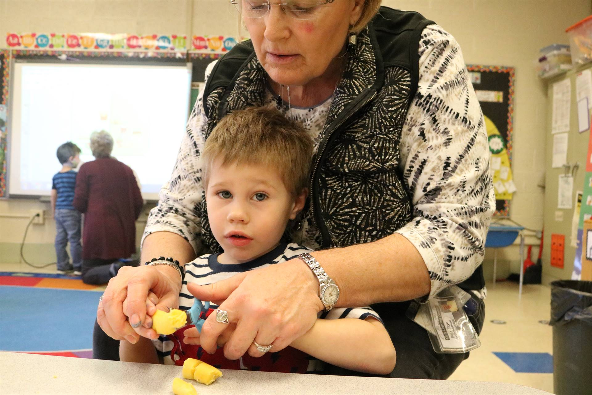 teacher helping boy cut playdoh