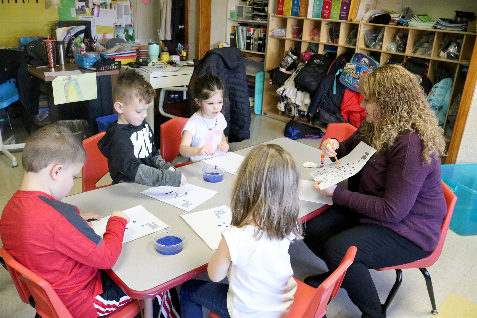 students and teacher sitting at table painting