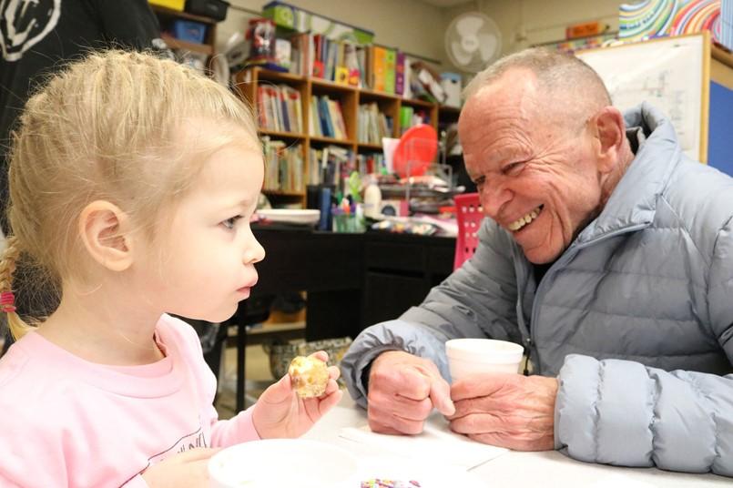 little girl eating donut with older guy