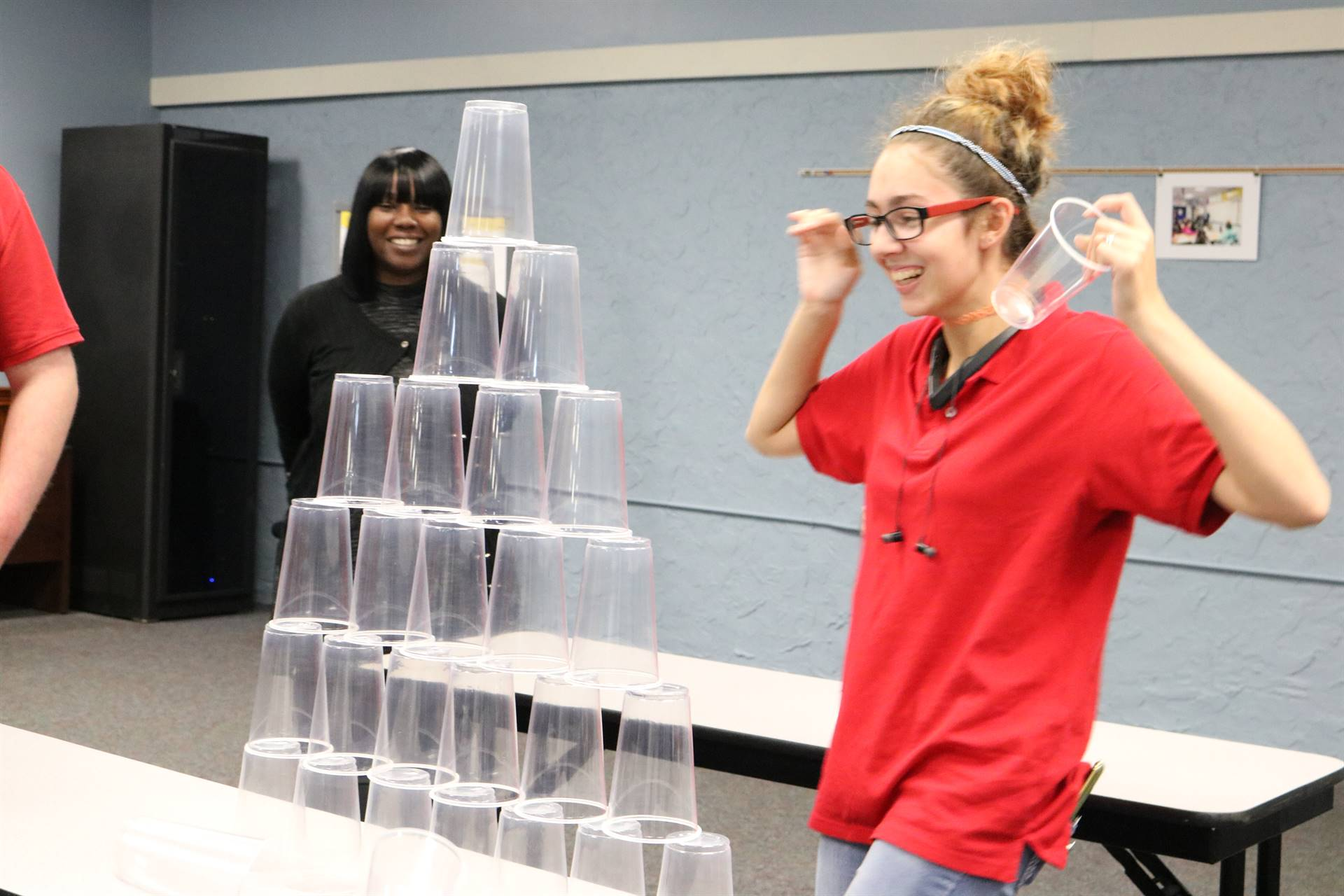 girls standing by cup tower