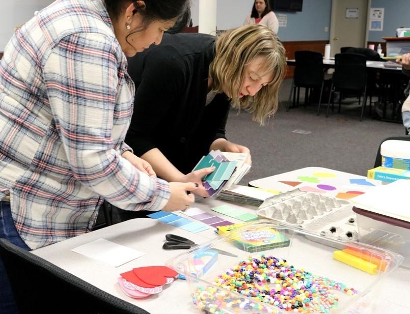 2 ladies sorting thru color samples