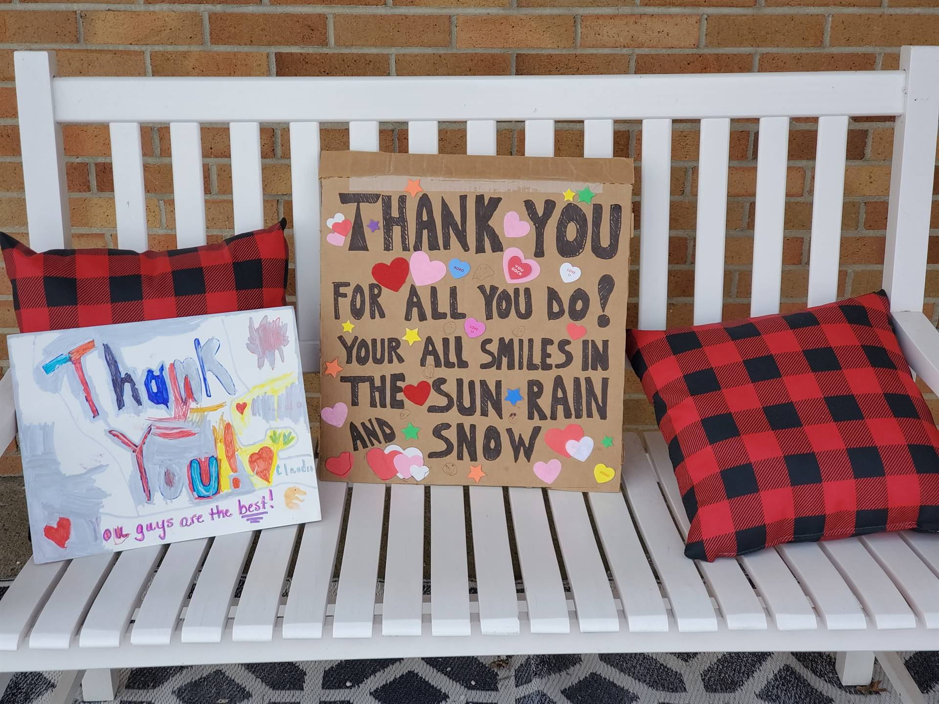 2 thank you signs sitting on bench