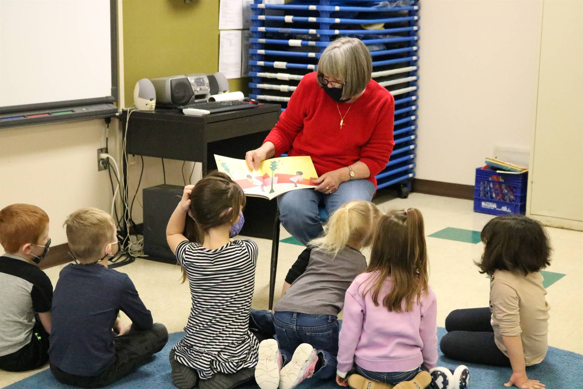 lady reading a book to kids
