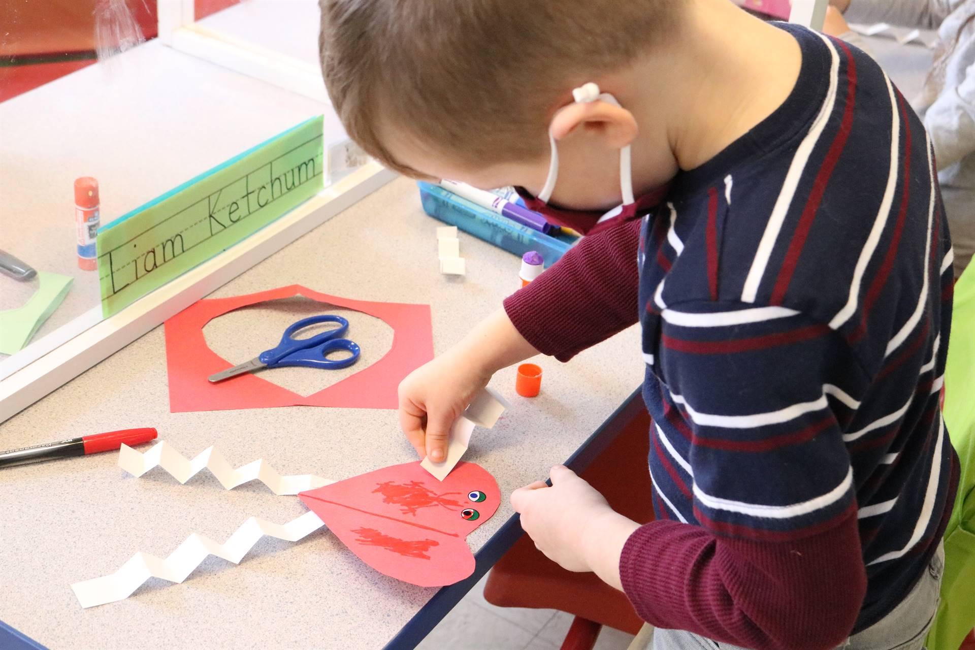 boy gluing to a paper heart