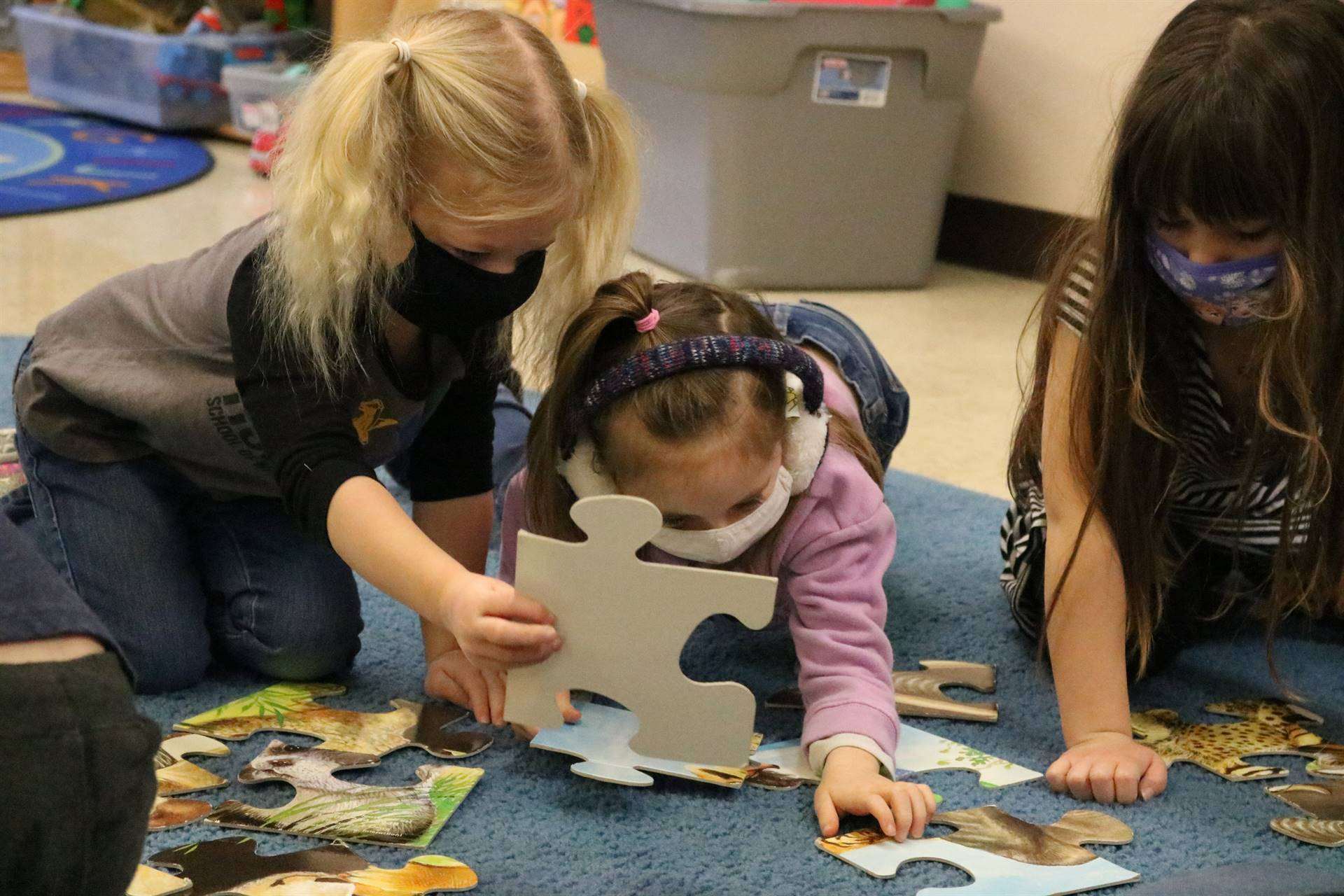 3 girls working on puzzle