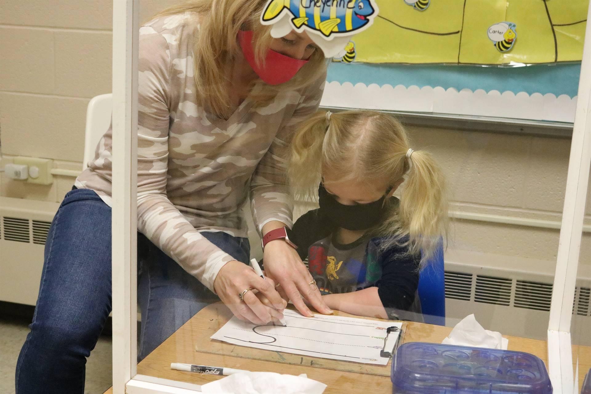 teacher helping girl write