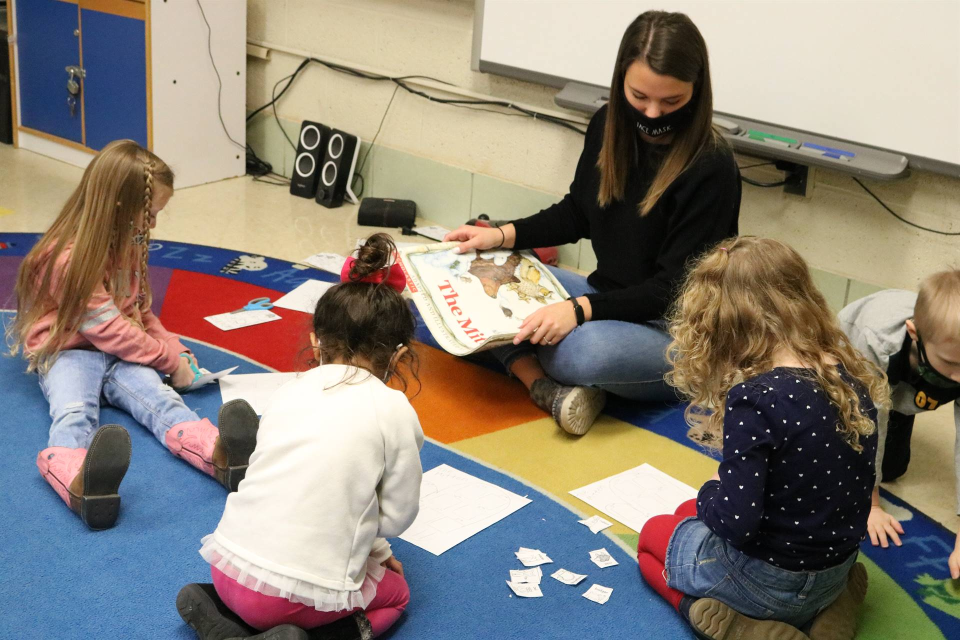 lady reading to 4 kids