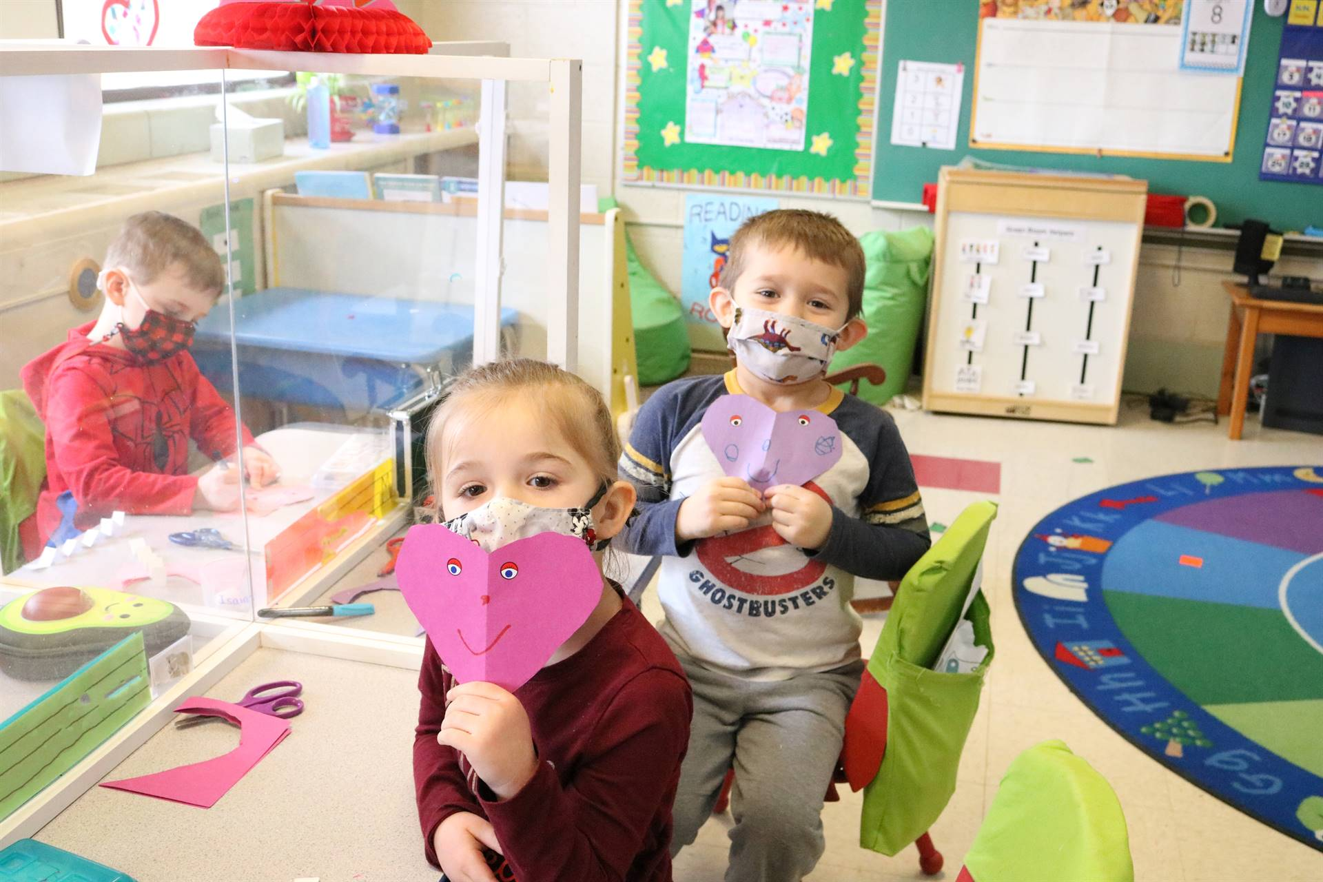 girl and boy holding heart papers