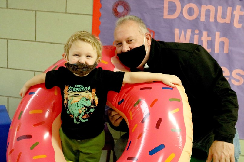 littl boy with older man and inflatable donut