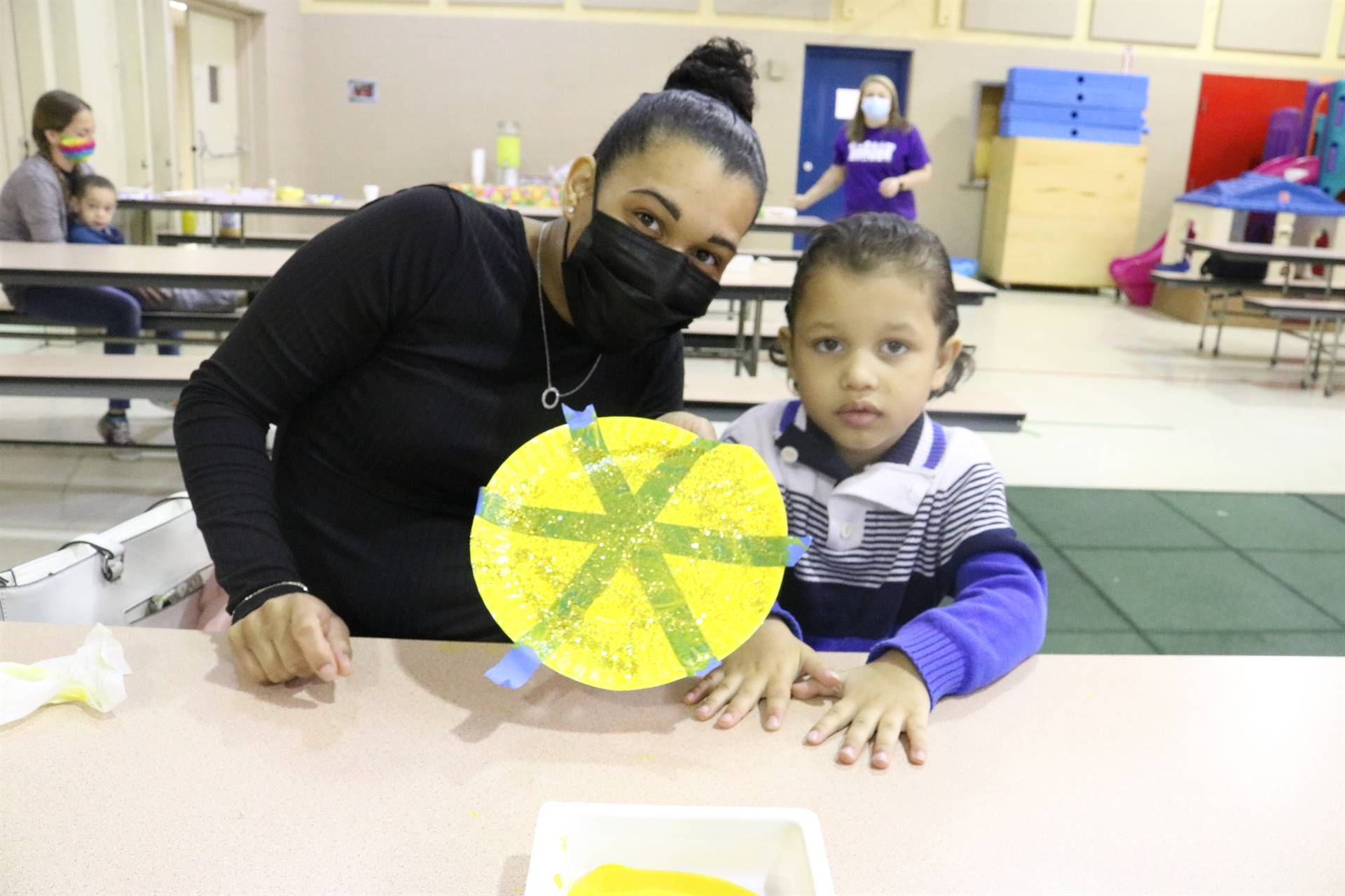 lady and boy holding yellow plate