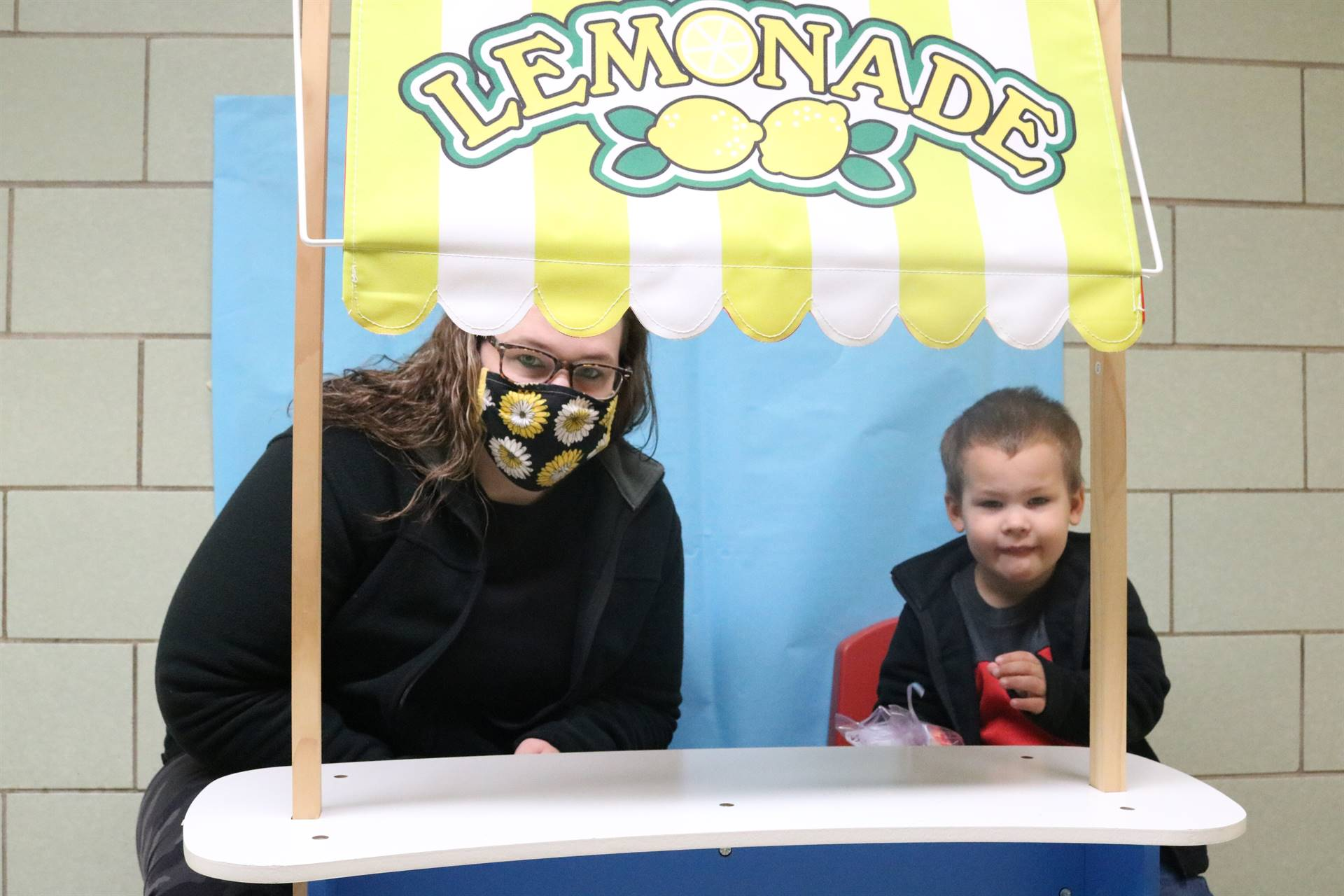lady and boy sitting at lemonade stand