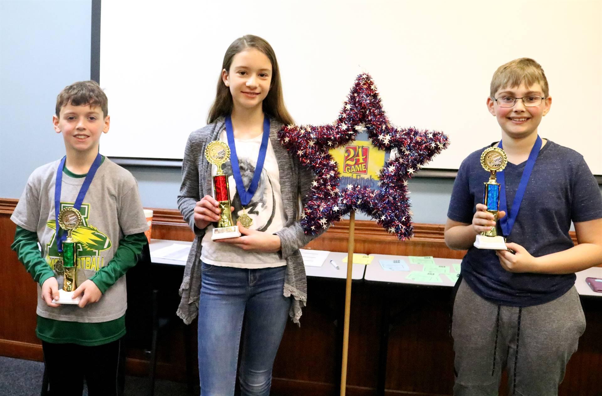2 boys, 1 girls holding trophies