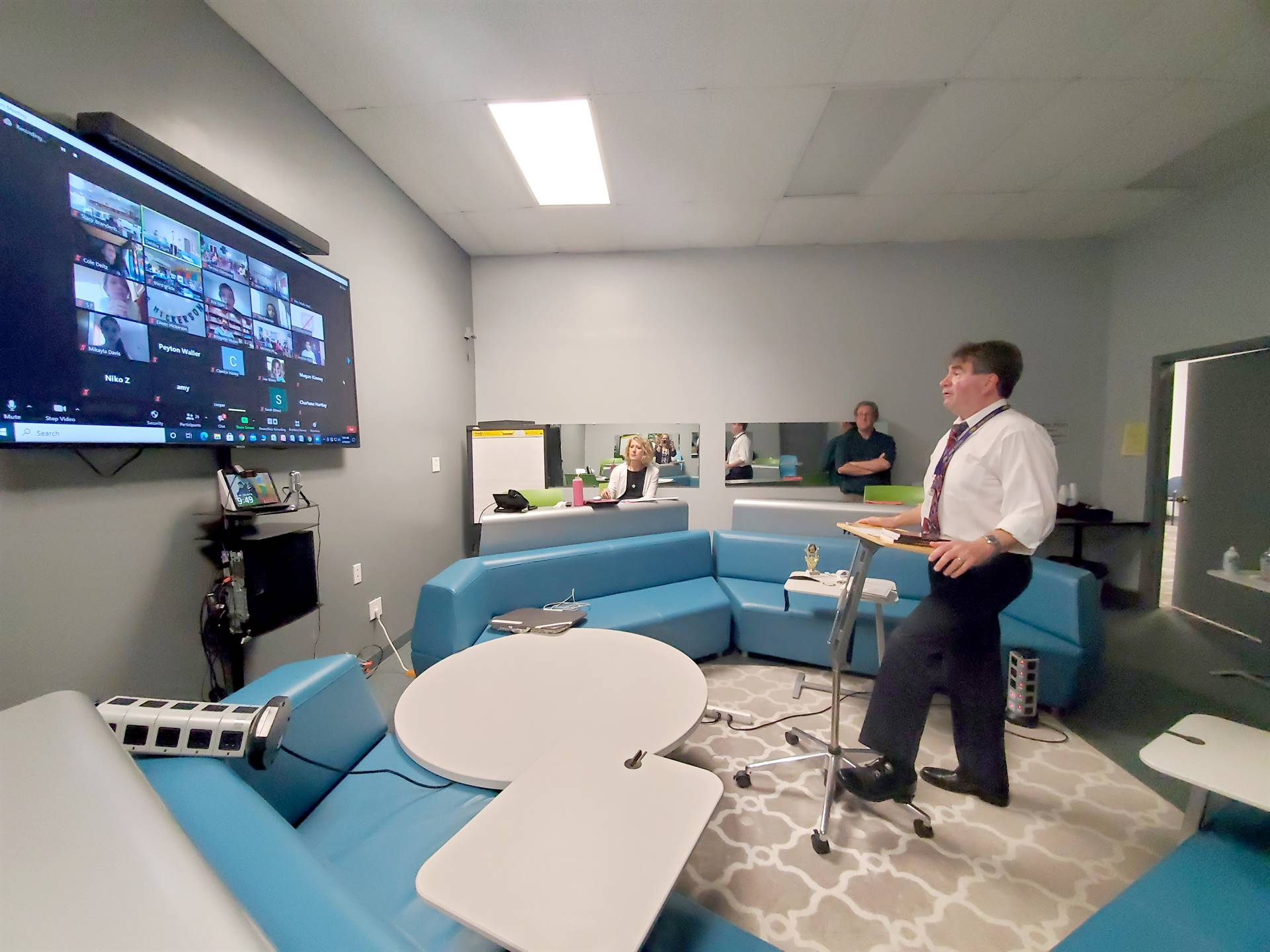 man standing looking at tv screen