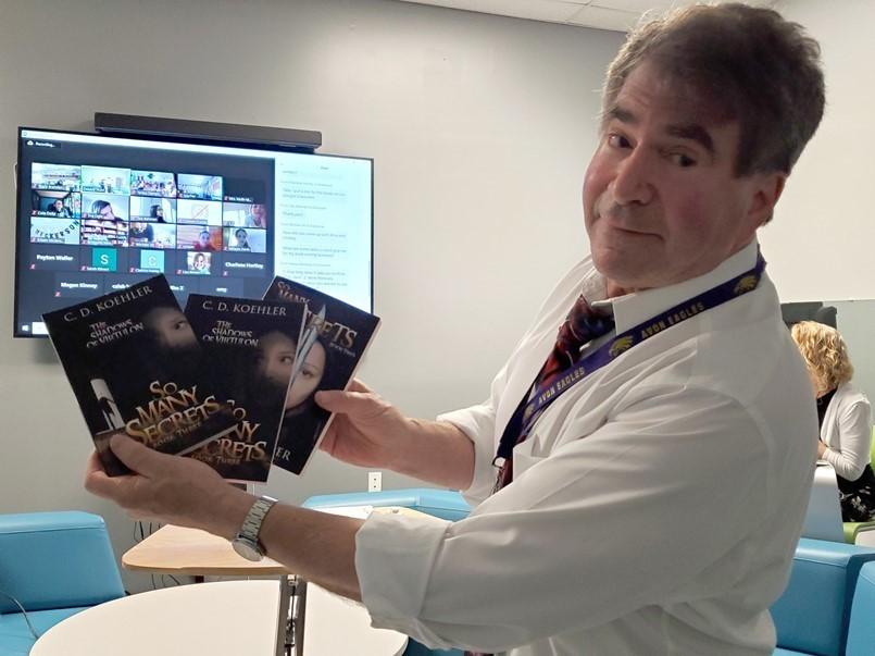 man holding 3 books